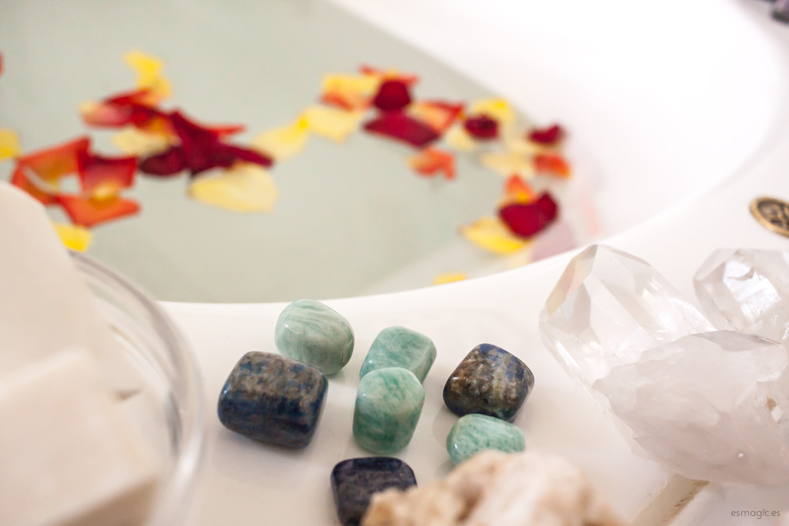 imagen de un baño con minerales de amazonita, lapislázuli, jabón natural y pétalos flotando en el agua de la bañera
